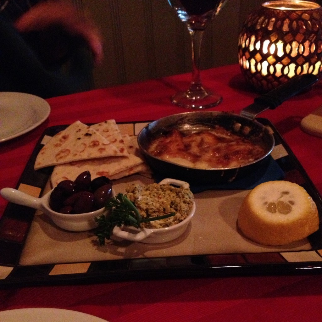 Saganaki with olives and olive spread, lemon and pita bread