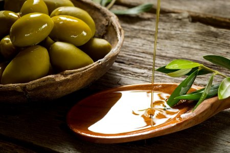 Olive Oil poured into a wooden dish next to a bowl of olives